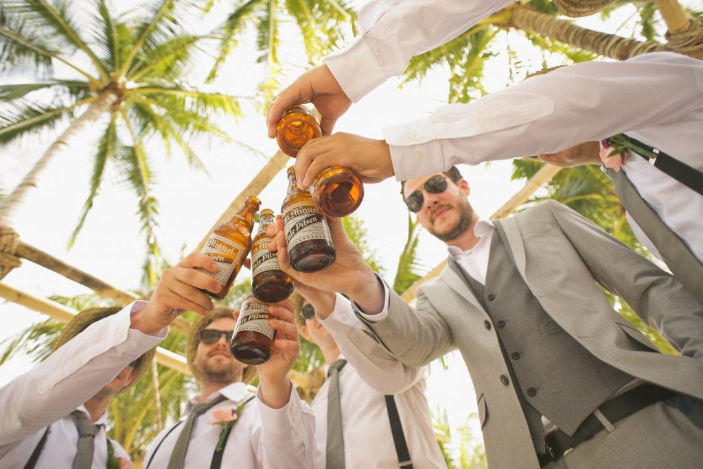 Groom celebrates with ushers on wedding day drinking beers