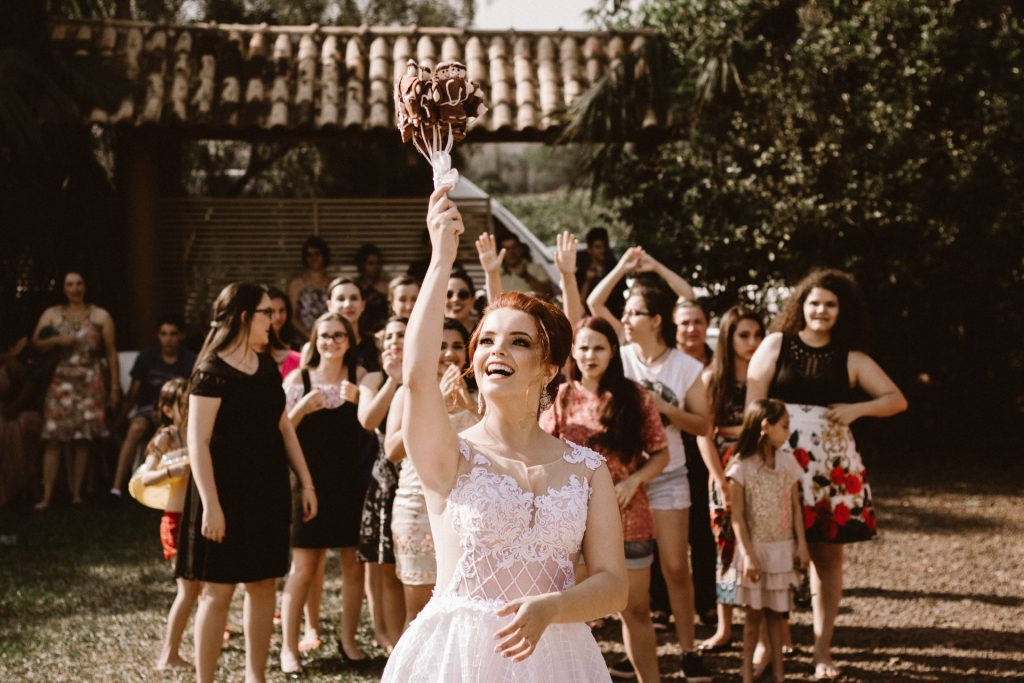 Bride about to toss bouquet in white dress on wedding day