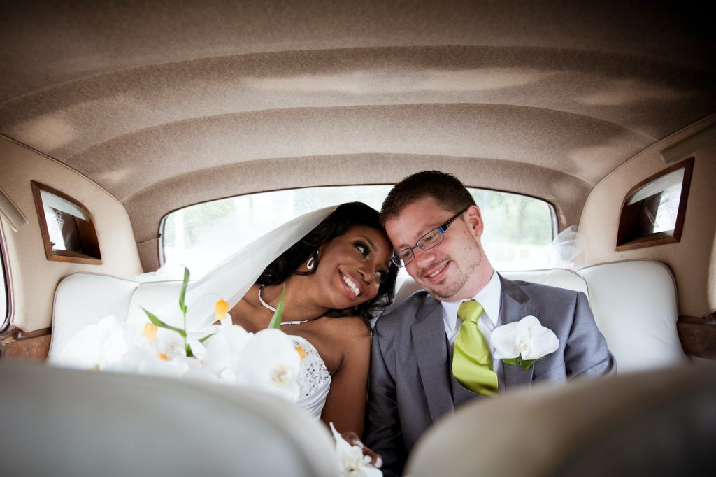 Bride and groom smile in wedding car after ceremony