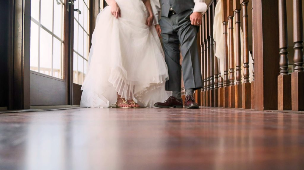 Bride shows flat shoes under wedding dress