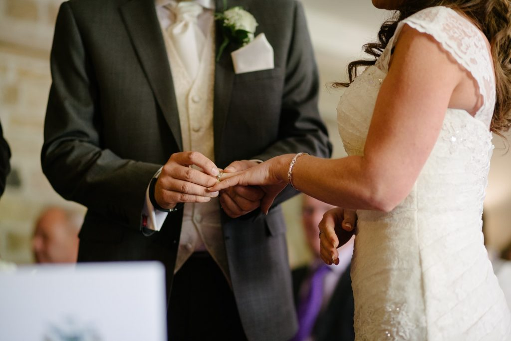 Bride and Groom exchanging rings at their wedding ceremony