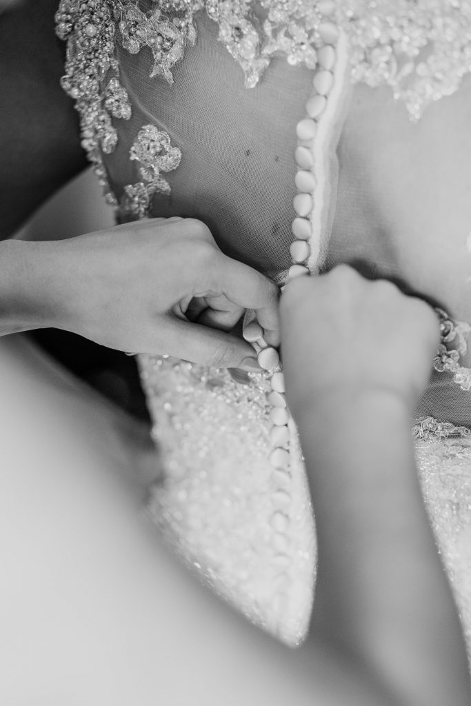 Bride getting buttons fixed on back of wedding dress