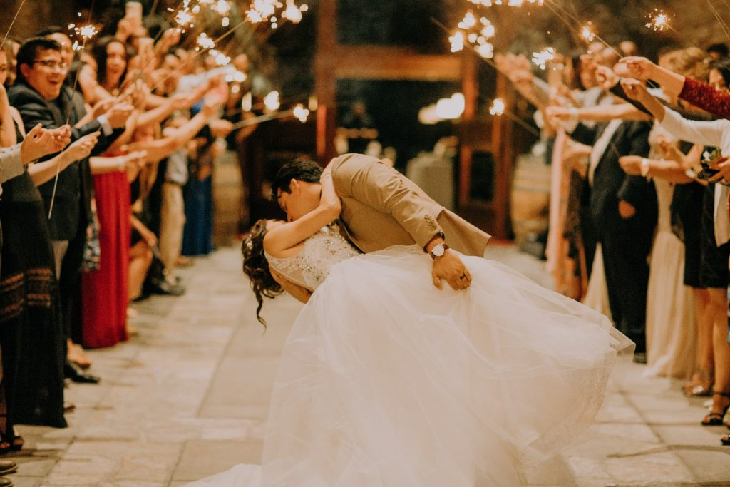Wedding guests create sparkler archway for Bride and Groom