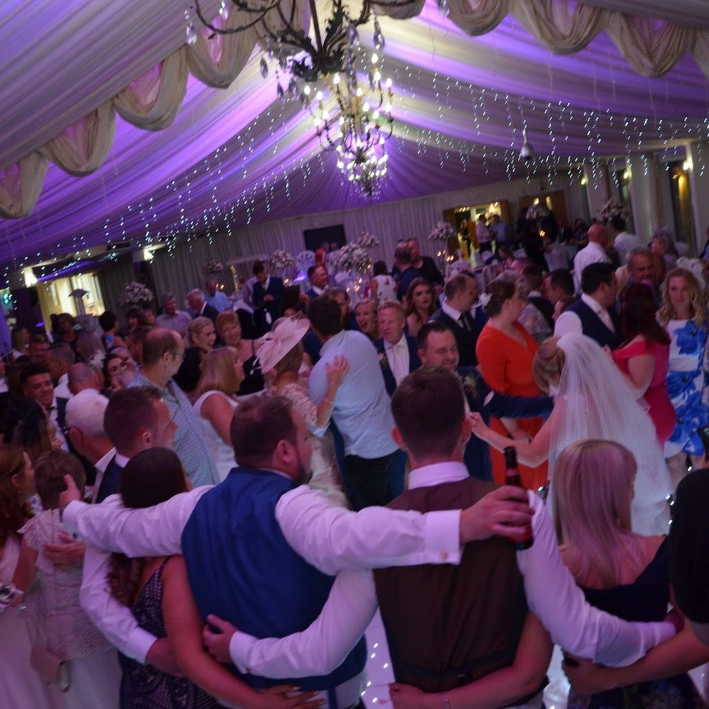 Wedding guests dancing on white LED dance floor