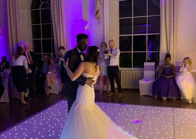 Bride and Groom First Dance on white led dance floor with purple uplighters