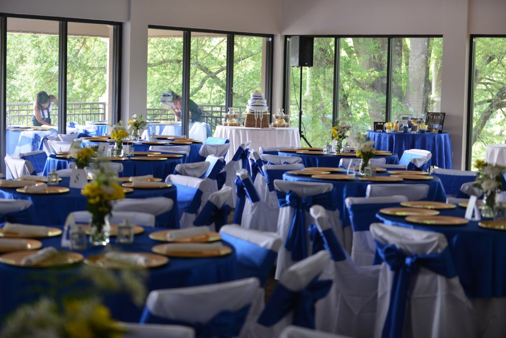 Wedding breakfast room laid out with white chair covers and blue sashes
