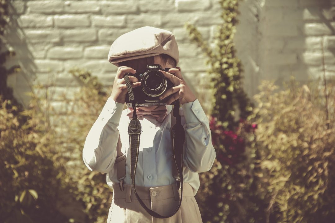 Young boy poses with camera at wedding