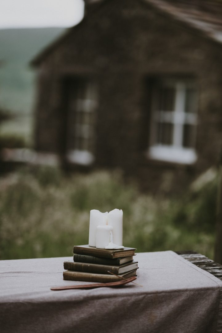 Wedding table centre pieces - pile of books with candles