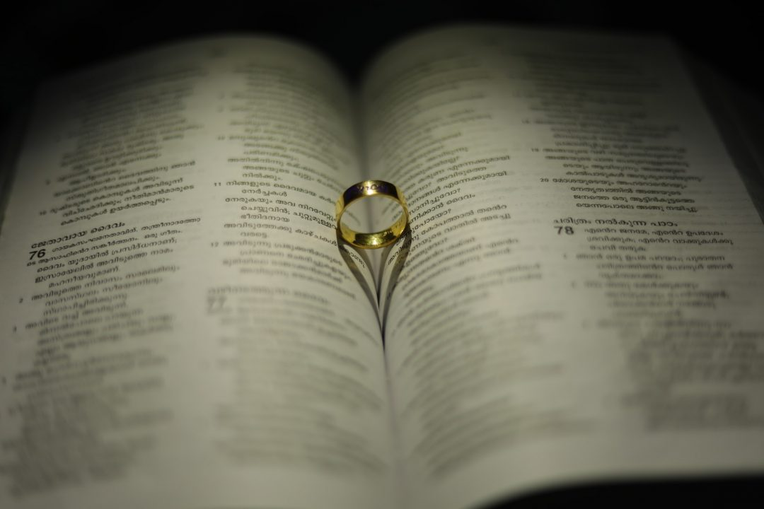 Gold wedding ring creates heart shadow on page of book