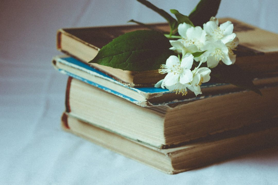 Pile of books with white flowers for wedding table centres