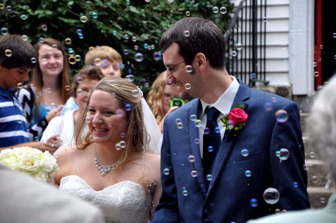 Smiling bride and groom surrounded by wedding guests and bubbles