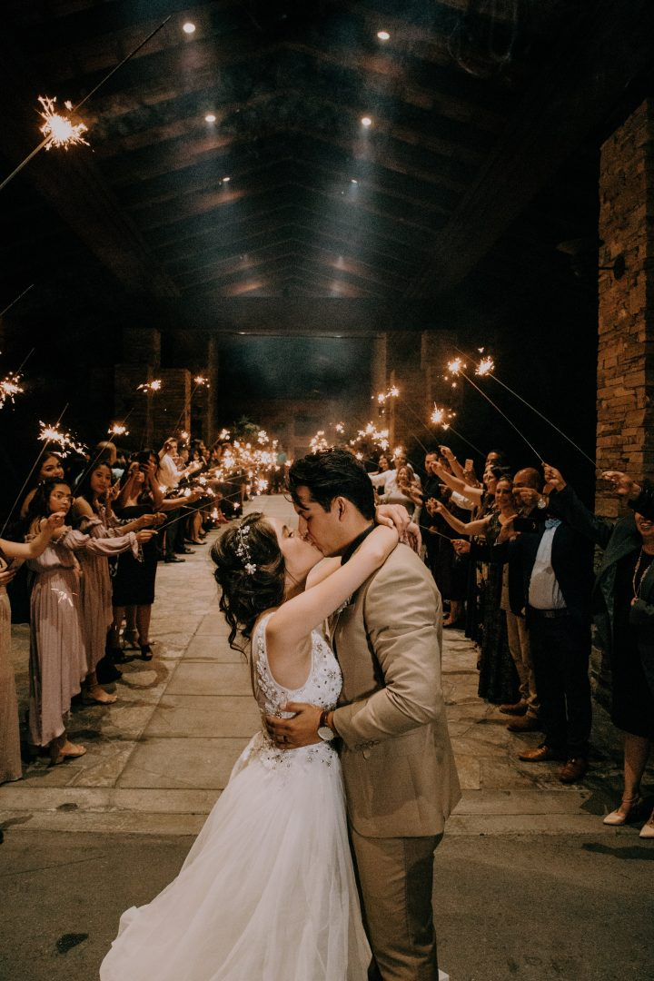 Bride and groom share a kiss while wedding guests wave long sparklers