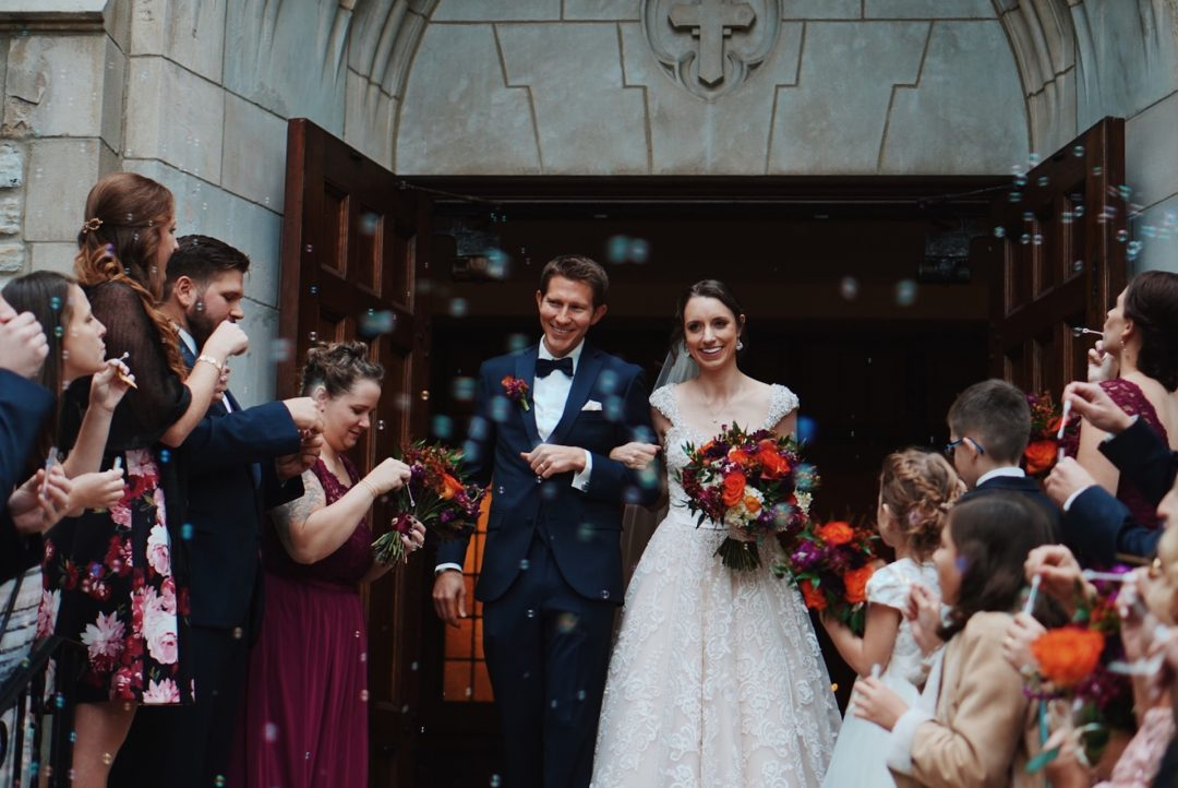 Wedding guests blow bubbles for newly married couple