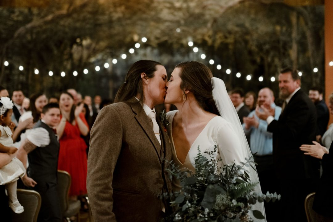 Wedding ceremony kiss with guests in background