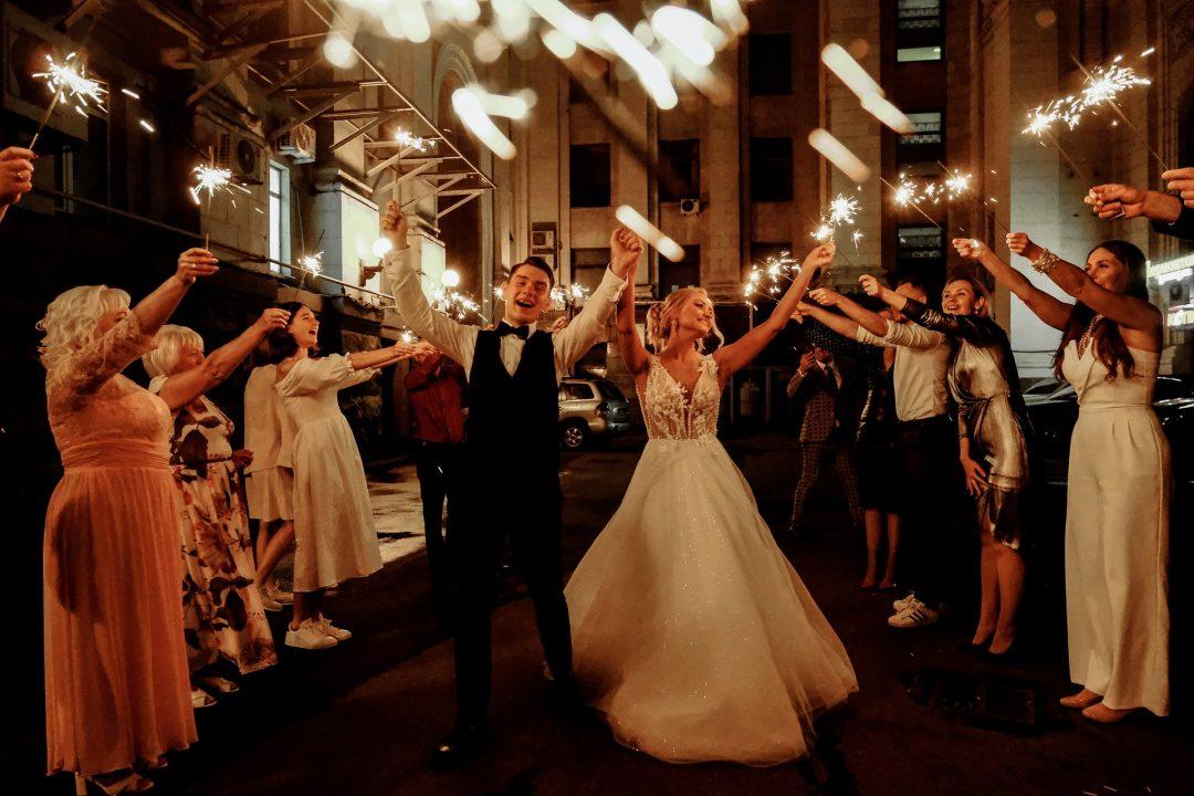 Wedding guests wave sparklers for Bride & Groom