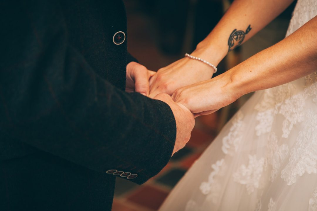 Bride and groom holding hands during wedding ceremony