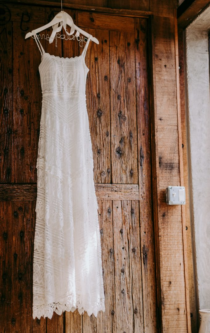 Delicate styled wedding dress with personalised hanger against old wooden door