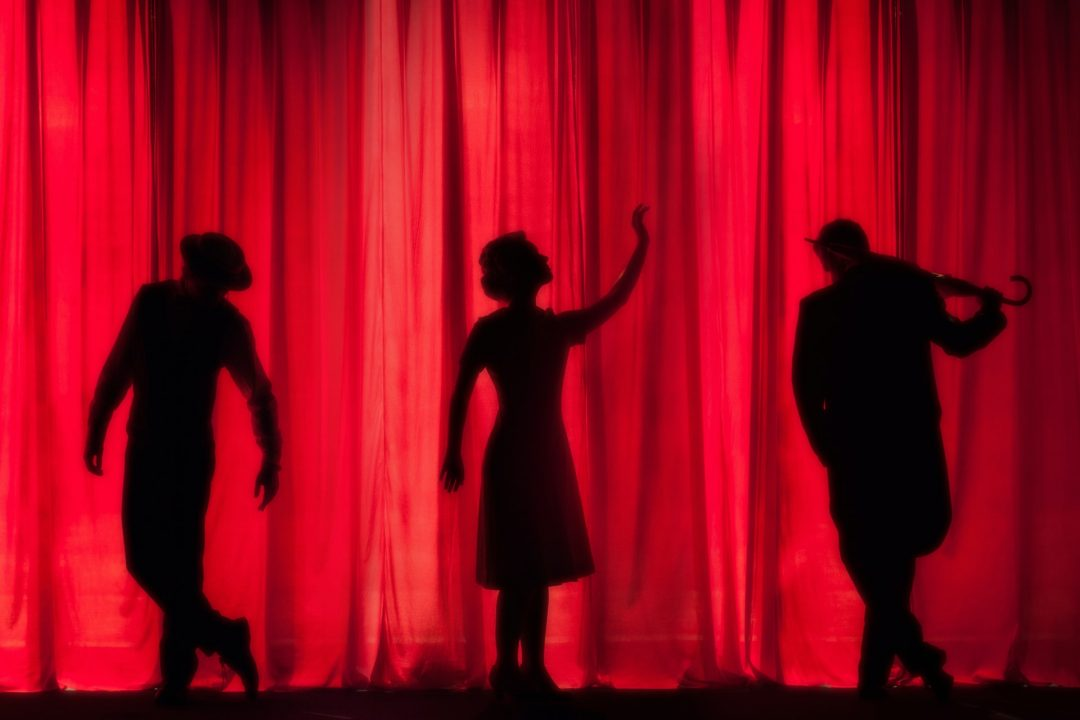 Red curtain with silhouettes at theatre