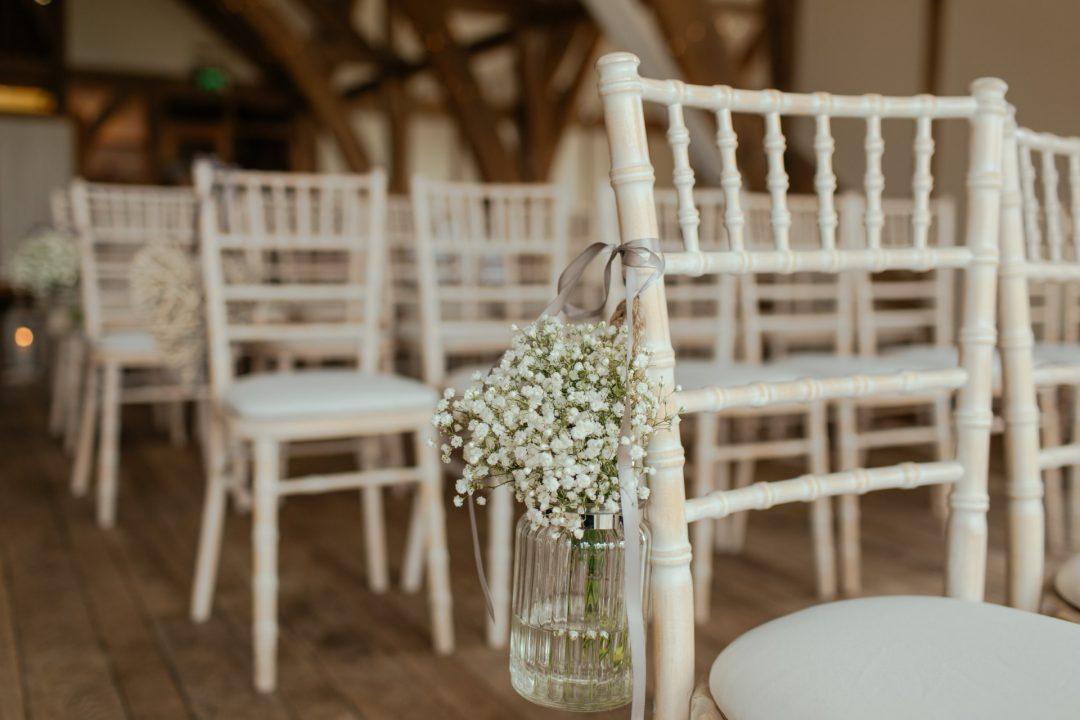 Wedding ceremony with white rustic seating chairs