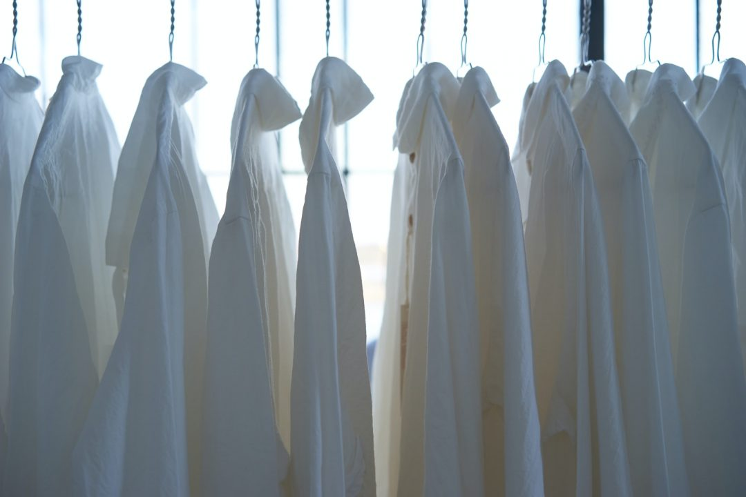 Selection of white wedding dress shirts on wire hangers
