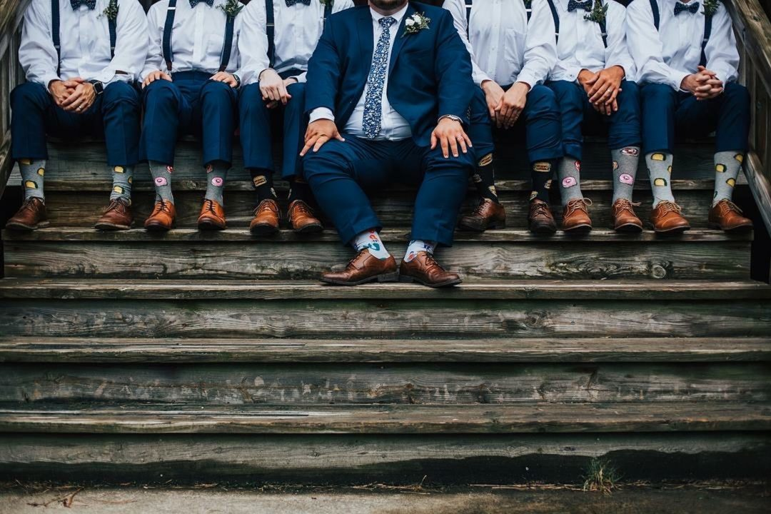 Groomsmen and ushers sitting on steps ahead of wedding ceremony