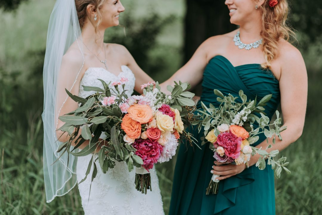 Bride with maid of honour and bright wedding flowers