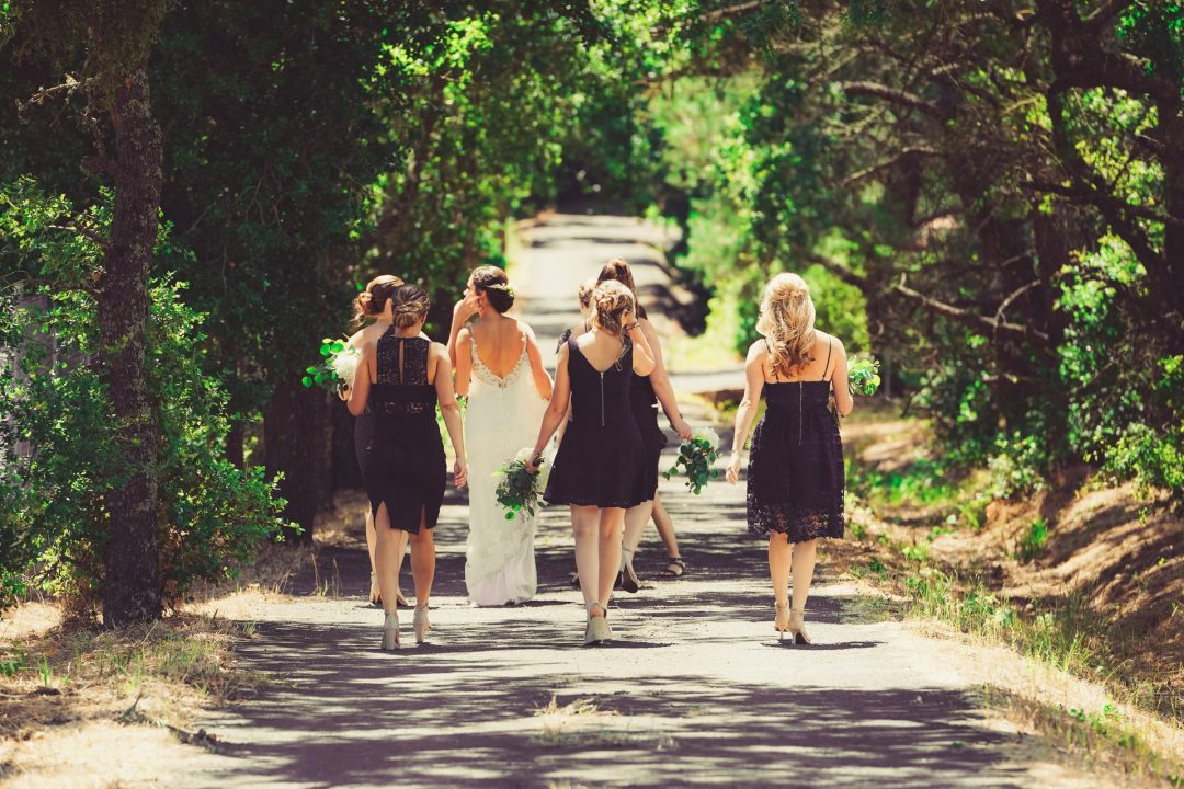 Bride walking outside to rustic wedding with bridesmaids