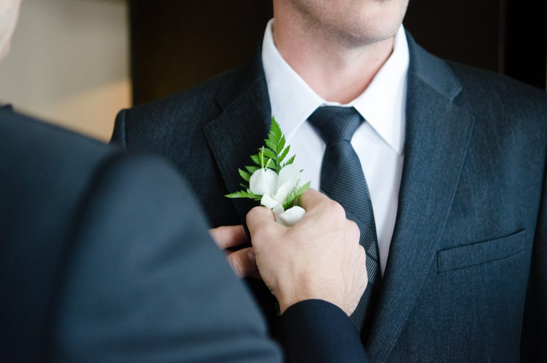 Best man helps groom with button hole flowers