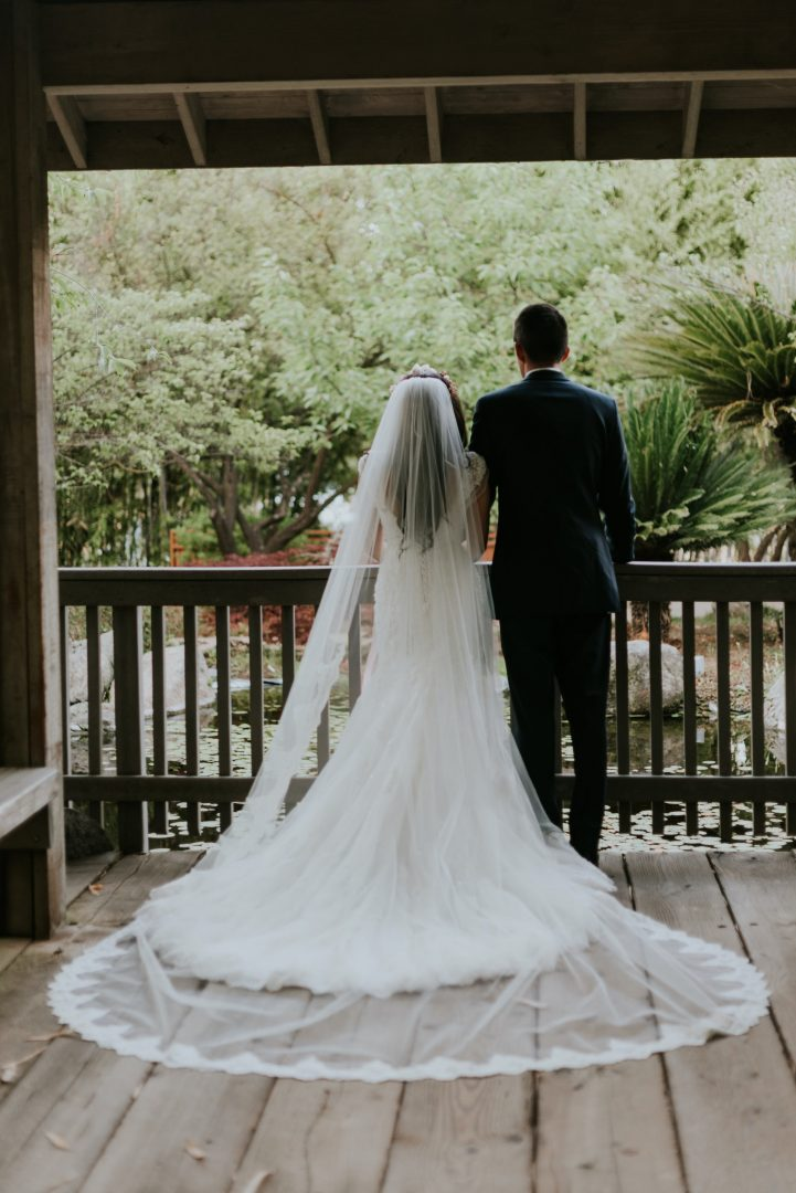 Bride with long white dress standing outdoors with groom