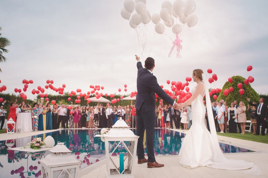 Bride and groom releasing balloons at outdoor wedding