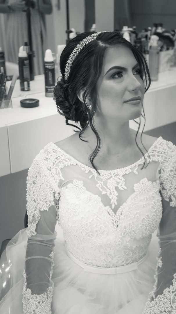 Wedding morning bridal prep - bride sits in white lace wedding dress