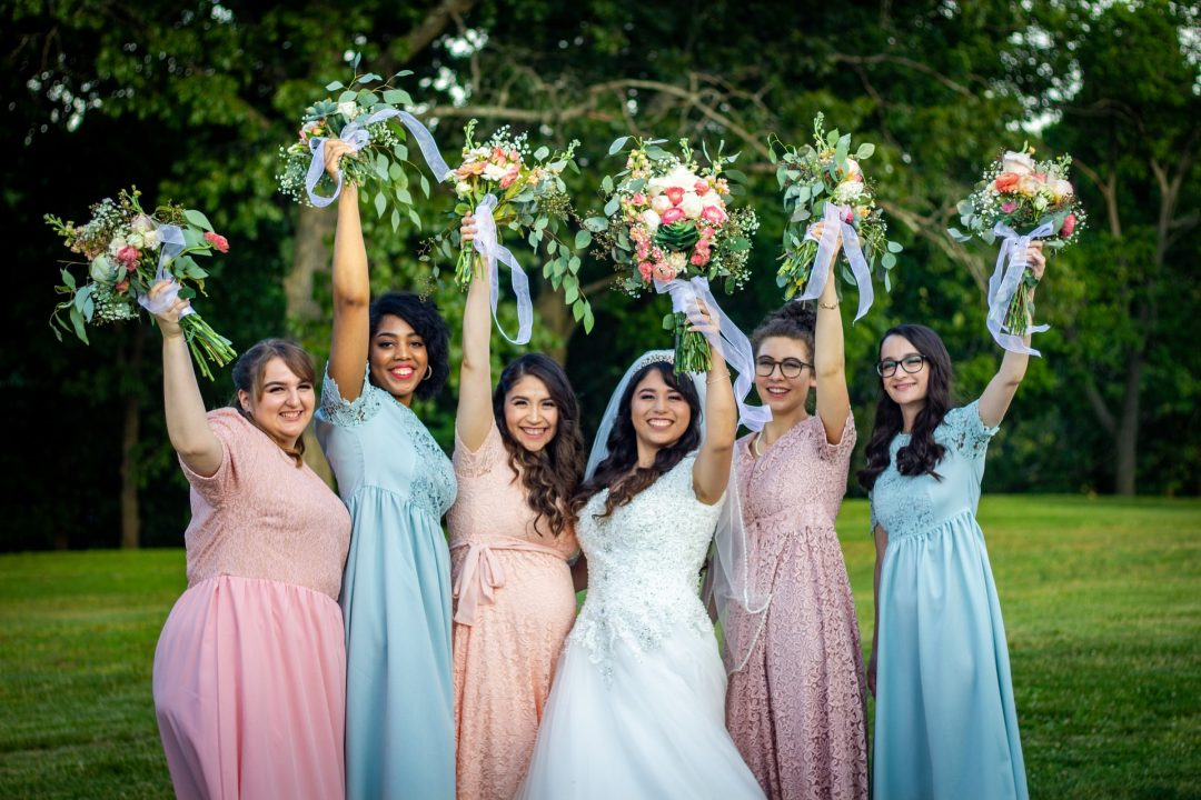 Bridesmaids lined up in pastel coloured dresses