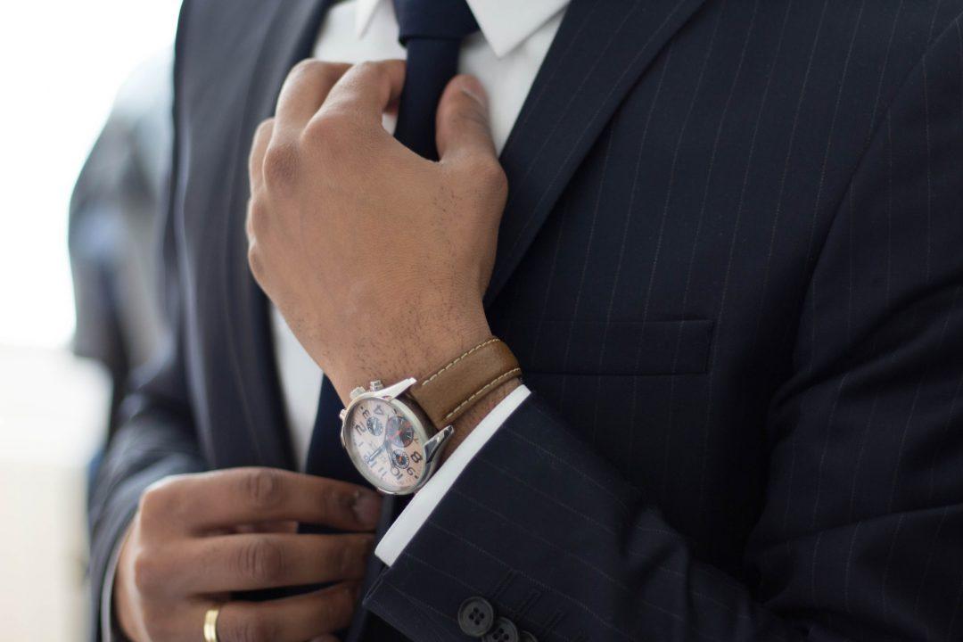 Well dressed groom adjusting tie before wedding ceremony