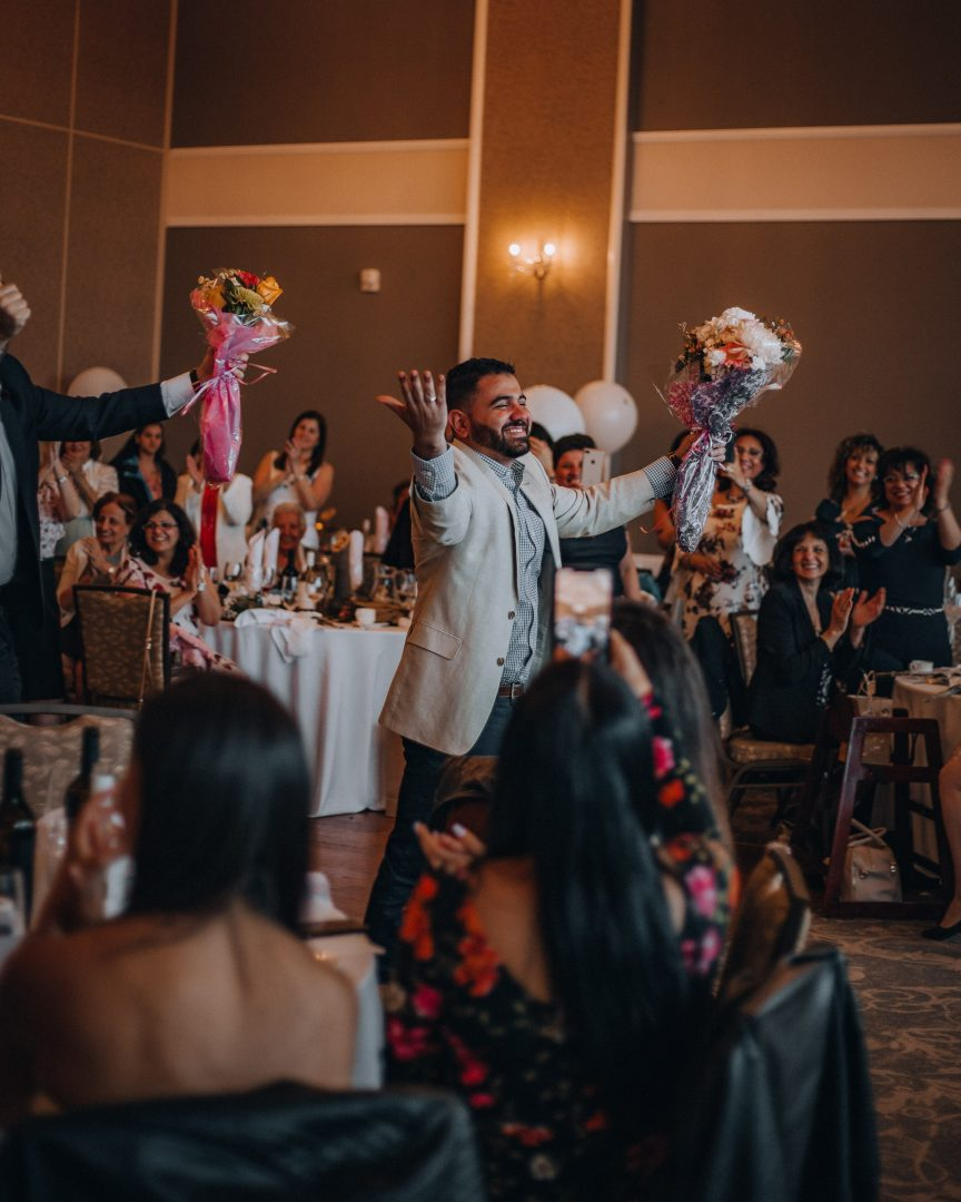 Wedding guests cheering with bouquet of flowers