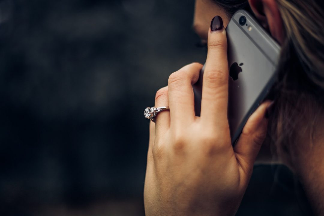 Bride to be with huge engagement ring talking on apple iphone